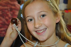 Girl holding a conker necklace