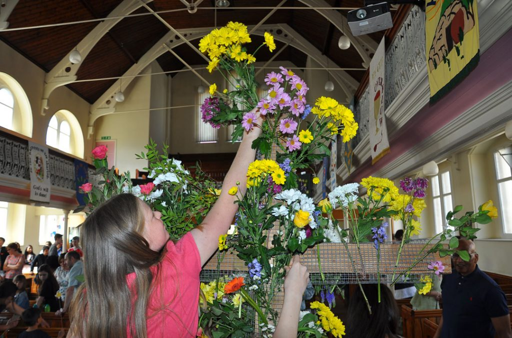 Church interior, with a girl decorating a large wooden cross with fresh flowers for Easter
