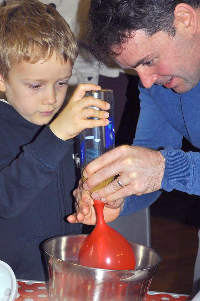 A father and son pour sand into a red balloon